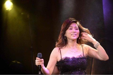 コンサートで歌っている黒いドレスを着た藤吉久美子の画像