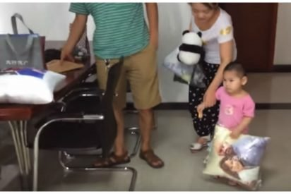 adopted orphan first meet 412x275.jpg?resize=412,275 - Little Girl Was Seen Carrying A Pillow With Photo Of A Couple Printed On It