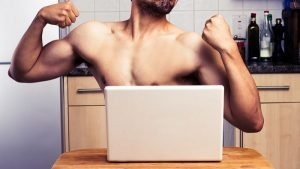 Naked young man is flexing his muscles as he's engaging in a webcam chat on his laptop