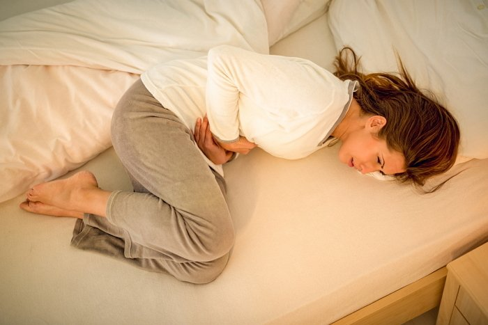 Beautiful young woman lying on bed and holding hands on her stomach.