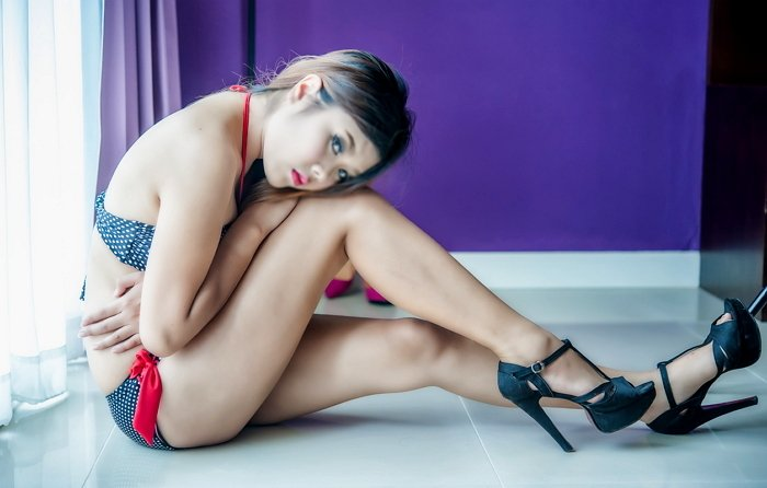 portrait of thai woman in black lingerie posing at window in hotel room
