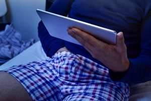 man with his hand under his underware while is watching his tablet
