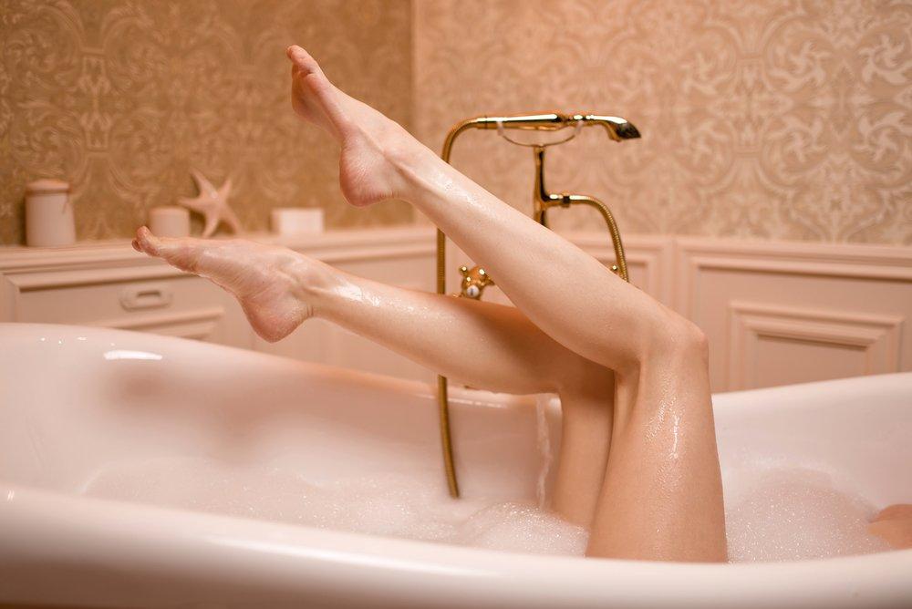 Woman in bath with foam showing legs