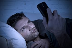 man in bed couch at home late at night using mobile phone in low