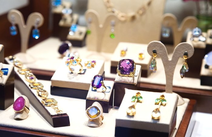 Gold jewelry with gems at showcase of jewelry shop