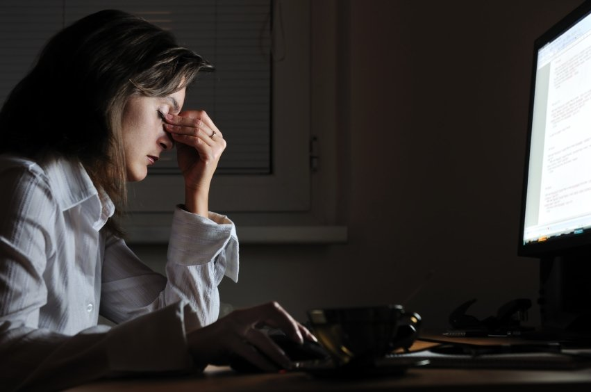 Young tired business woman with headache sitting at computer in workplace - night overtime work