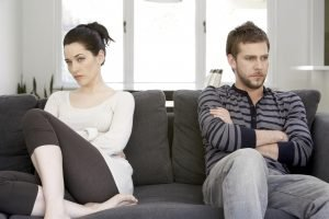 Couple sitting on sofa with arms folded, looking angry