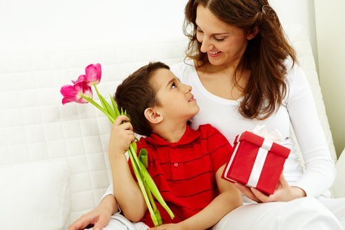 Cute lad with bunch of beautiful tulips looking at his mother with giftbox