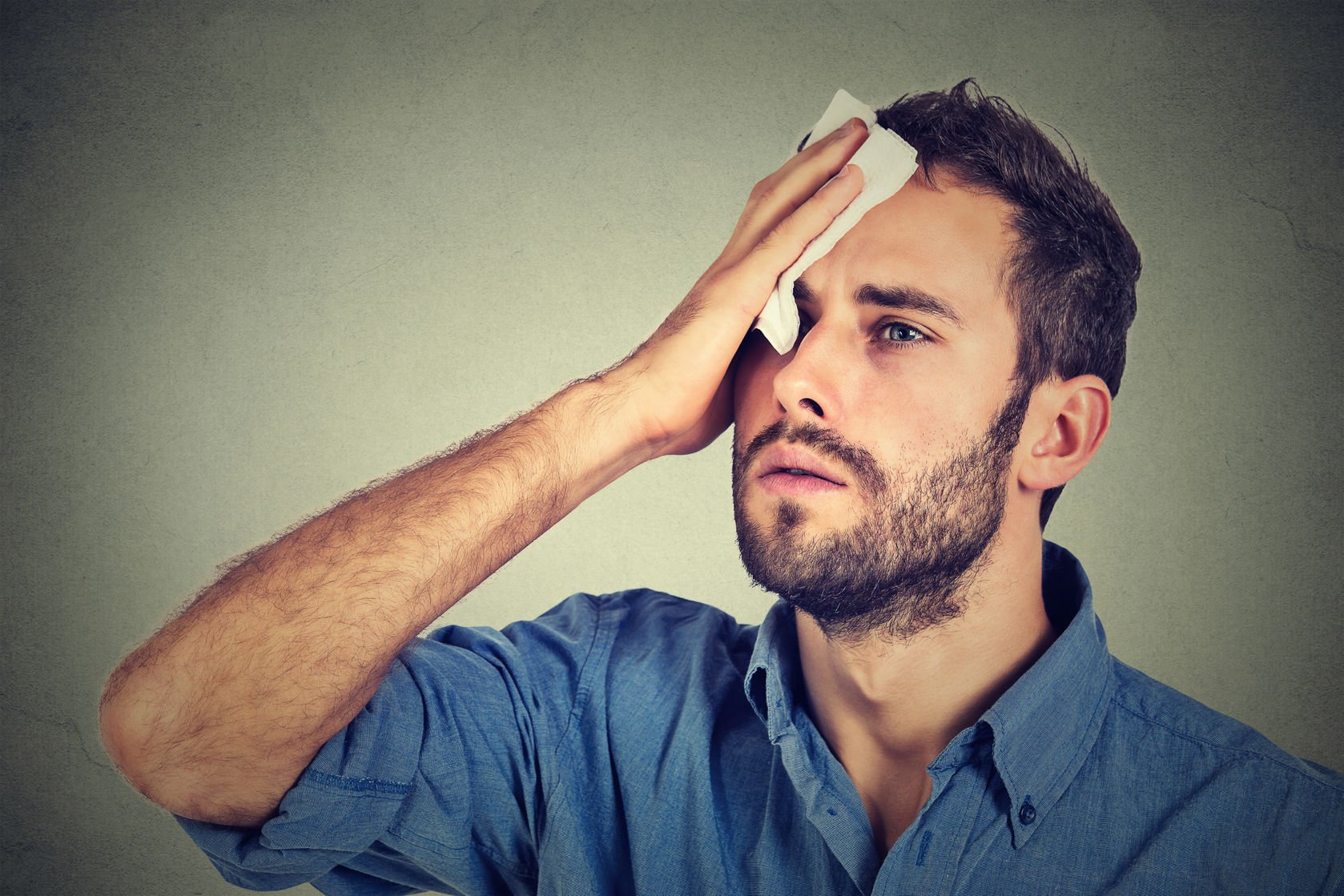 46737381 - tired man stressed sweating having fever headache isolated on gray wall background. worried guy wipes sweat on his face