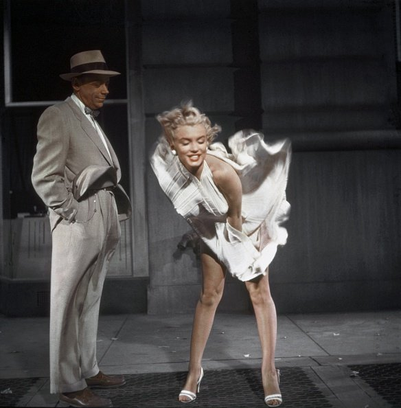"""LOS ANGELES, CA - 1954: Marilyn Monroe standing over a subway grate with her white dress blowing and co-star Tom Ewell looking on in 1954 during the filming of """"The Seven Year Itch"""" in Los Angeles, California. (Photo by Sam Shaw/Shaw Family Archives/Getty Images)"""