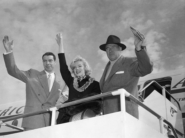 """(Original Caption) 1/29/1954-San Francisco, California: Waving despite a broken thumb, siren Marilyn Monroe prepares to leave the international airport with her husband Joe DiMaggio (L) and Frank O'Doul, manager of the San Diego Padres. They will appear at ceremonies opening Japan's baseball season, and Monroe will visit servicemen in hospitals in the Pacific theater. She says of the broken digit, she """"just bumped it against the door."""""""