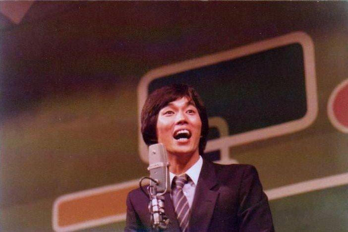 マイクの前でトークをしている若いころの明石家さんまの画像・壁紙