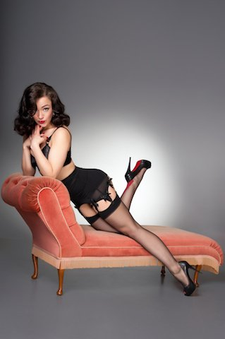 Attractive classic fifties pinup in black lingerie & stockings