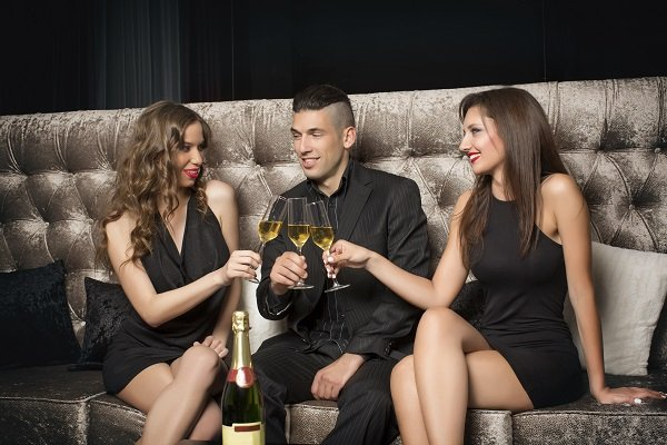 One man and two women celebrating with champagne in nightclub