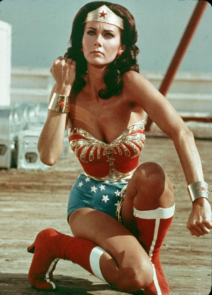 American actor Lynda Carter kneels on the ground and bears her forearm in a still from the television series Wonder Woman. (Photo by Warner Brothers/Getty Images)