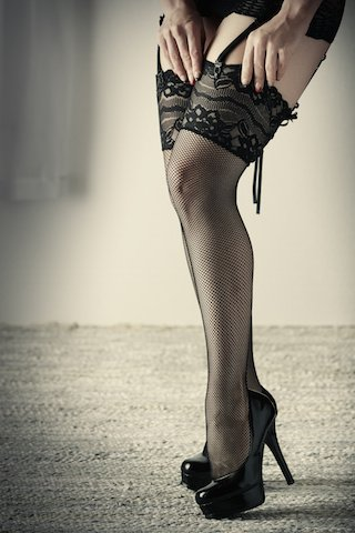 Beautiful, voluptuous and sexy caucasian adult woman in black fishnet stockings and garters in a boudoir setting lit from the side with window light.