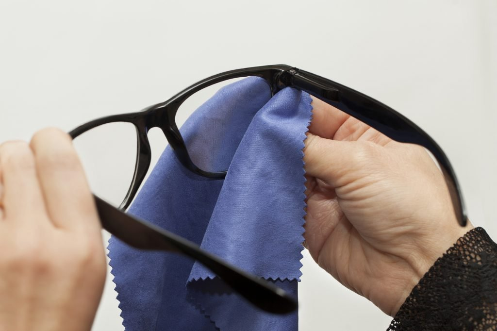 Woman trying to clean spectacles