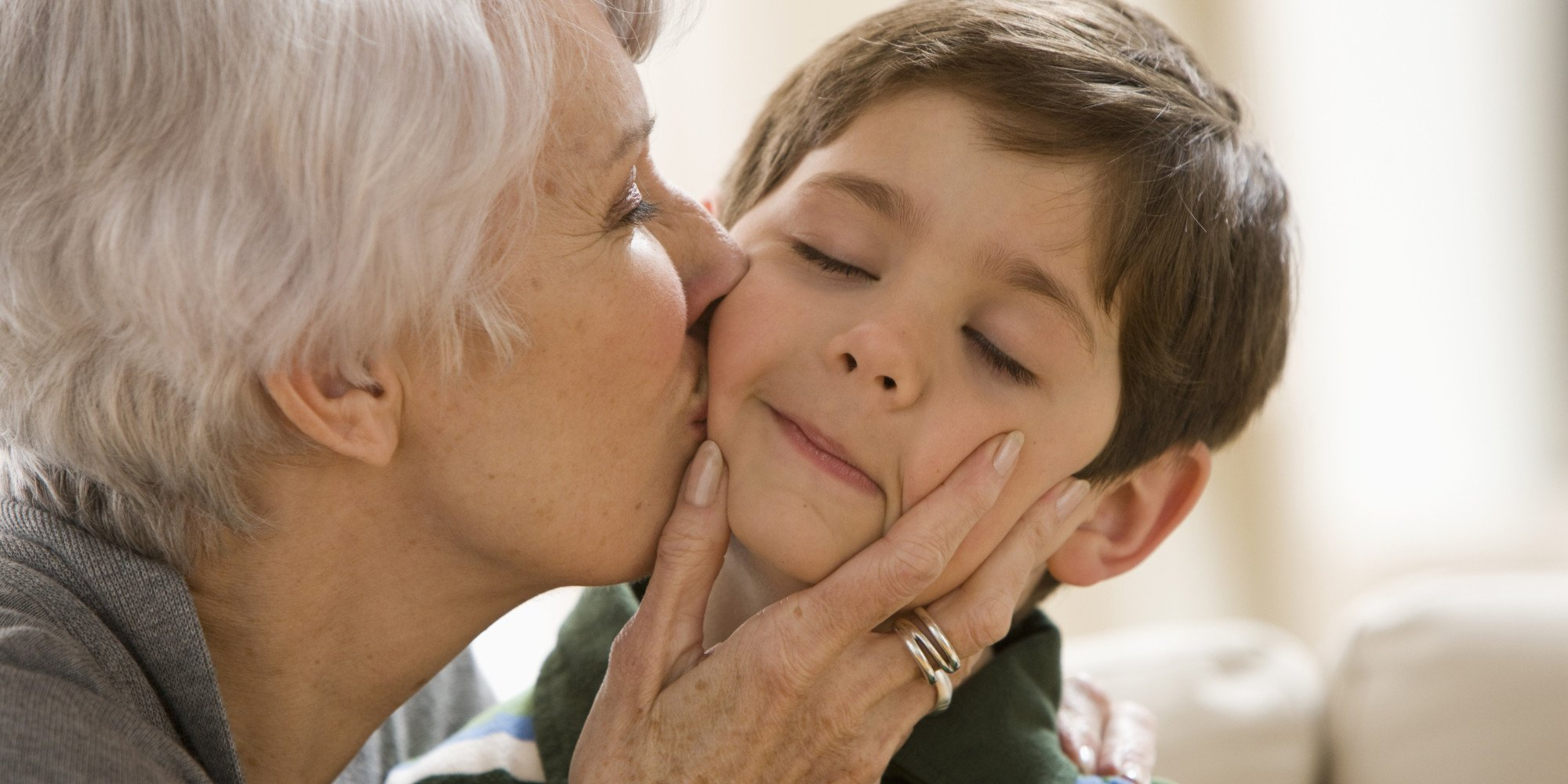 Caucasian grandmother kissing grandson