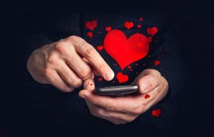 Man typing love text messages on a smartphone for Valentine's day. Selective focus on hands and phone device.