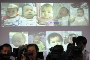 Surrogate babies that Thai police suspect were fathered by a Japanese businessman who has fled from Thailand are shown on a screen during a news conference at the headquarters of the Royal Thai Police in Bangkok August 12, 2014. Thai police said last Friday they had found four more babies they suspect were fathered by the Japanese businessman, bringing the total to 13 discovered in Bangkok that week. Surrogacy scandals have gripped Thailand after an international outcry over a Down Syndrome baby left with his Thai birth mother when his Australian biological parents took his twin sister back to Australia. REUTERS/Athit Perawongmetha (THAILAND - Tags: HEALTH SOCIETY)