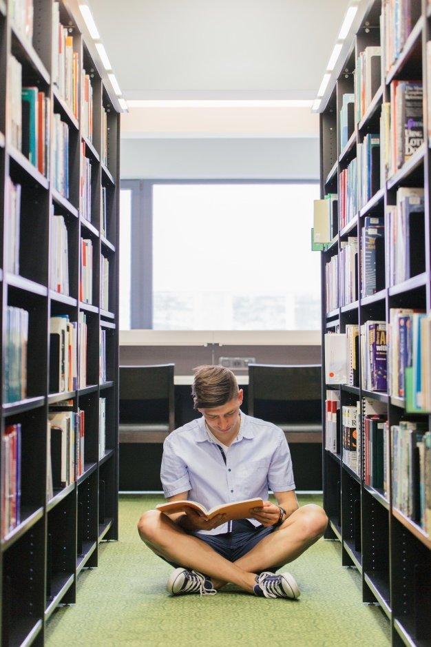 Srudent con libro sentado en el piso Foto Gratis