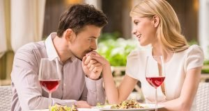 Young smiling couple enjoying the meal in gorgeous restaurant and drinking wine. Man kissing woman's hand.