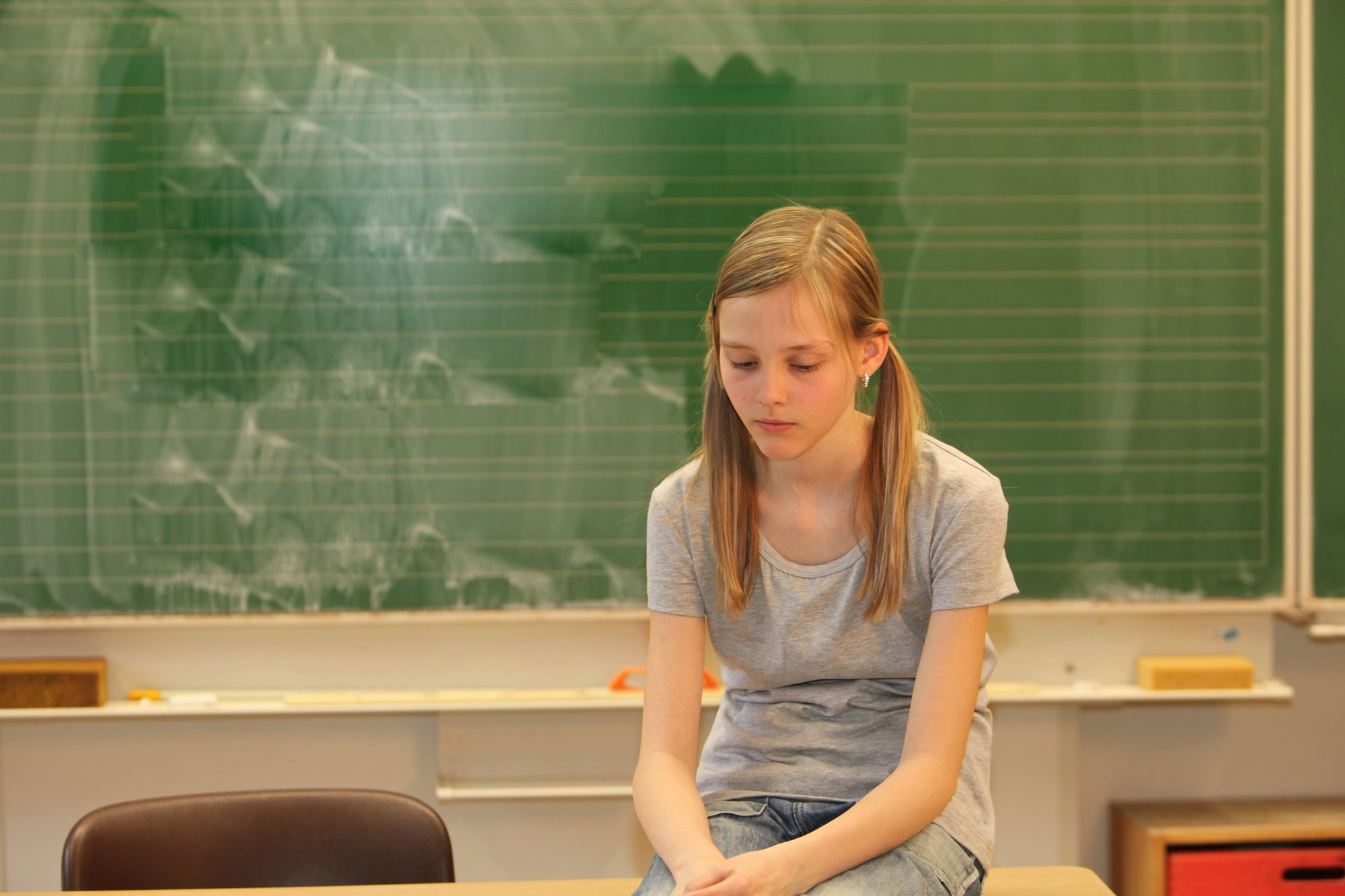 Sad blonde girl in school in front of a blackboard with his head down
