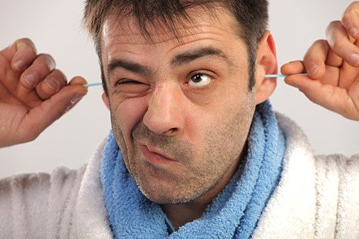 Man cleaning his ears with cotton swab