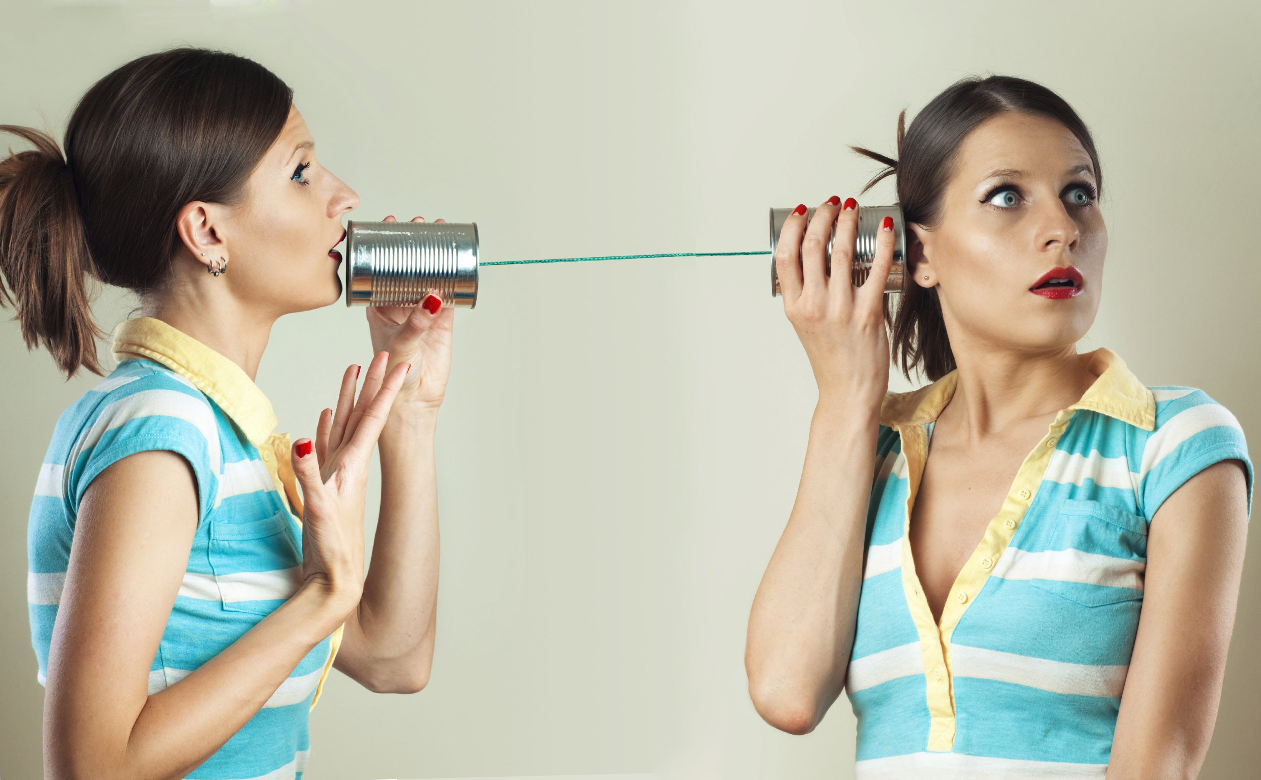 a young woman talking to herself on the tin can phone