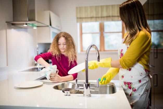 madre-ayudando-a-su-hija-en-la-placa-de-lavado-en-la-cocina_1170-2831