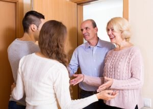 meeting-door-positive-young-couple-inviting-elderly-parents-to-come-inside-49360589