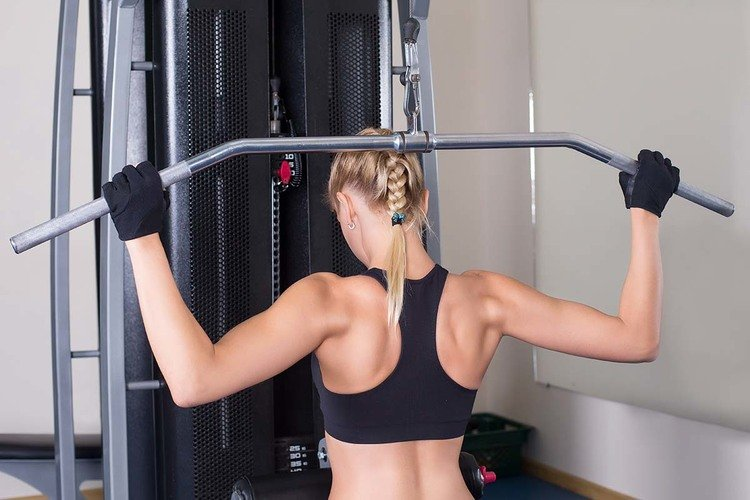 Athletic woman performing back exercise in gym
