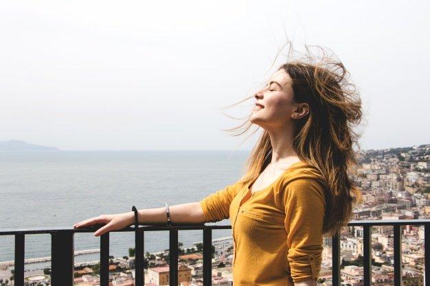 mujer-disfrutando-aliento-de-viento_23-2147670157