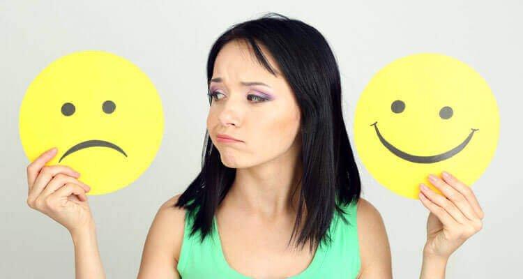 mulher-com-emoticon-triste-e-emoticon-alegre