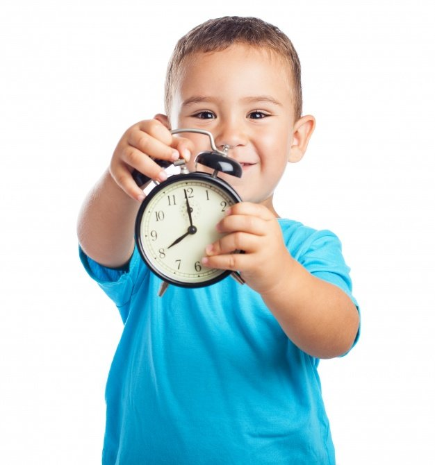 nino-sonriente-mostrando-un-reloj-despertador_1187-2837