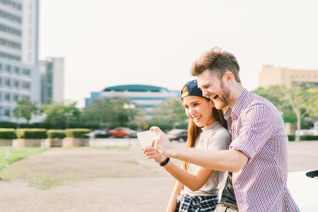 74109466 - happy multiethnic couple taking selfie during sunset in the city, fun and smiling, love or gadget technology concept