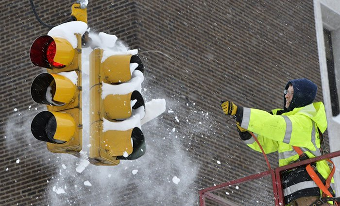 City Of Erie Traffic Engineering Employee Uses Compressed Air To Clear Snow From A Traffic Signal