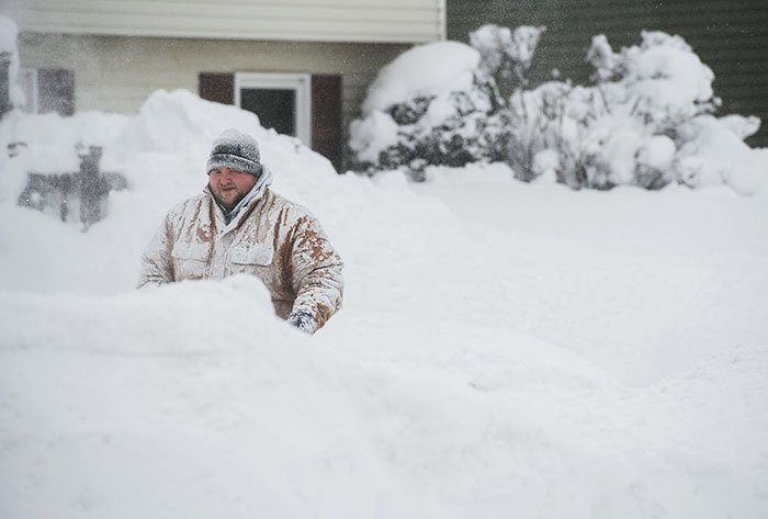 A Man Removes Snow From The Sidewalk In Front Of His Home After Two Days Of Record-Breaking Snowfall In Erie, Pennsylvania