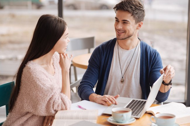 This our profit. Handsome youthful man presenting some information to his female partner while sitting at cafeteria during lunch break.