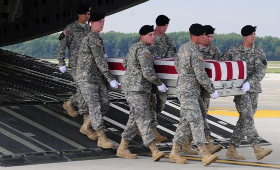 Soldiers from the 3d U.S. Infantry Regiment (The Old Guard), assist in a somber transfer of Sgt. James L. Skalberg Jr., 25, of Cullman, Ala., assigned to 4th Battalion, 1st Field Artillery Regiment, 3rd Brigade Combat Team, 1st Armored Division, Fort Bliss, Texas, and another Soldier, June 30, at Dover Air Force Base, Del.