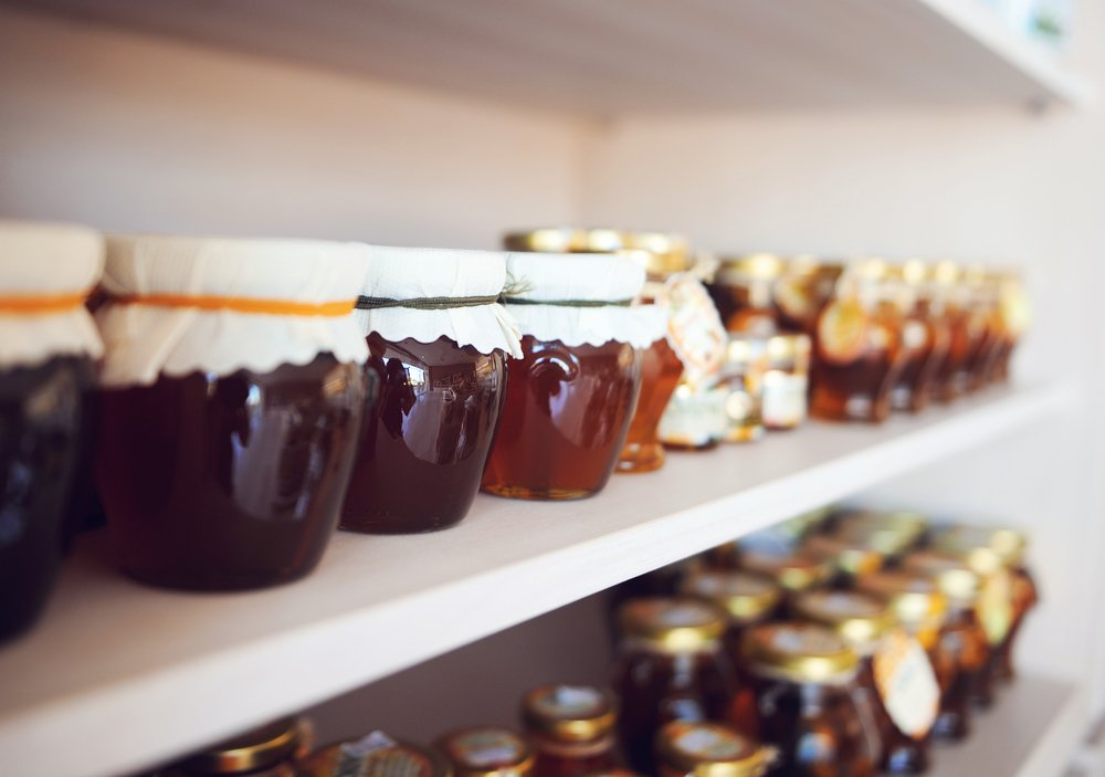Assorted honey and jams in glass jars on a shelf
