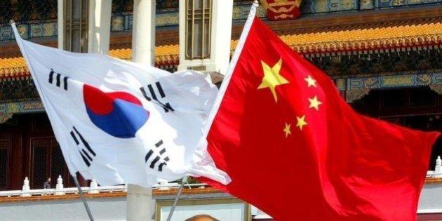 6月20日、浜田・イェール大学名誉教授ら18人が日中韓3カ国の関係改善を求める報告書を首相官邸に提出しようとしたところ、受け取りを断られていたことが明らかに。写真は中韓の国旗。北京で2003年7月撮影(2014年 ロイター)