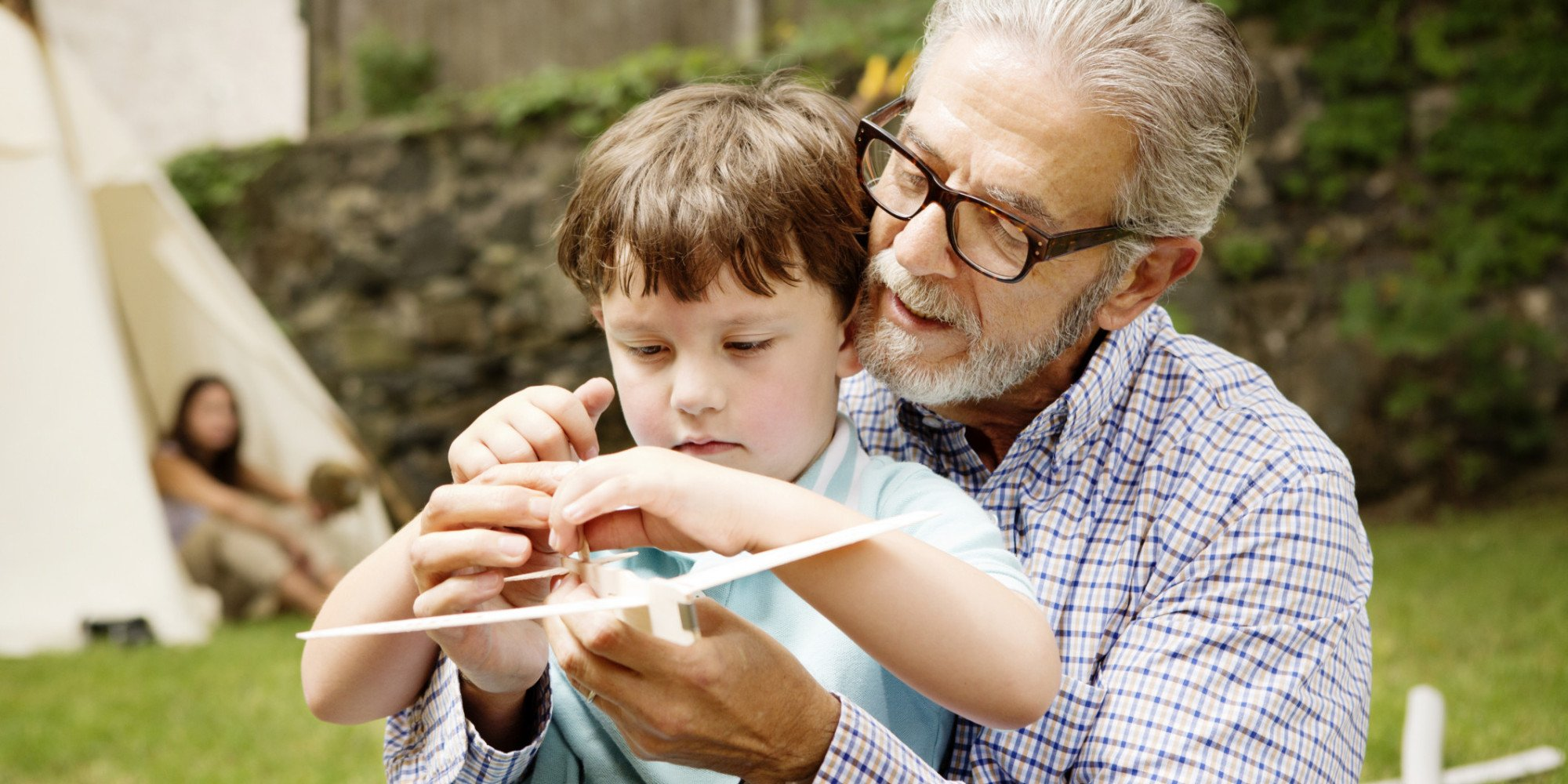 Grandfather and Boy Playing with Model Airplane