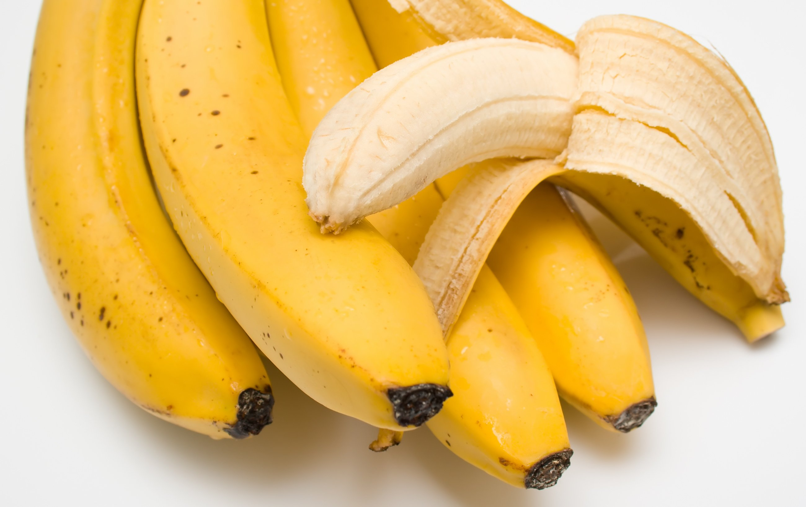 Cluster of ripe bananas. One banana is cleared away from a peel.