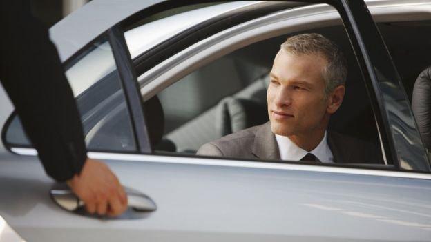 Homem em carro de luxo