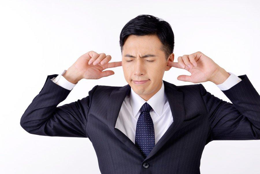 フリー写真 耳に指を突っ込んで耳を塞ぐビジネスマン
