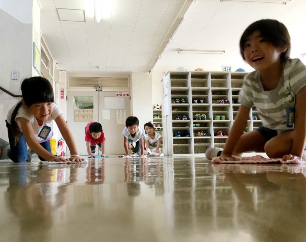 Tokyo, Japan - September 2 - 2016: Elementary school students are cleaning their classroom and school. In Japan students do the cleaning in the mornings and and after lunch except the toilets and teachers room.