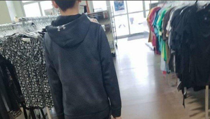 Anthony, de 13 años, entra al negocio que vende ropa usada para comprar sus propias prendas.