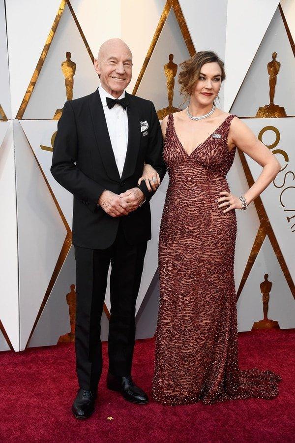 Patrick Stewar y Sunny Ozell se hicieron presentes en la gala de los Oscar. Él impecable black tie con moño de terciopelo y zapatos acordonados de cuero y su mujer lo acompañó con un vestido bordeaux escote V bordado. De joyas eligió pulsera, anillos, gargantilla y aros.