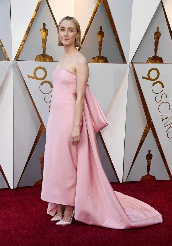 Saoirse Ronan apostó por rosa chicle. Su diseño exclusivamente hecho a medida por la firma Calvin Klein. Strapless y con un gran moño y stilettos en punta que completaban el soñado outfit